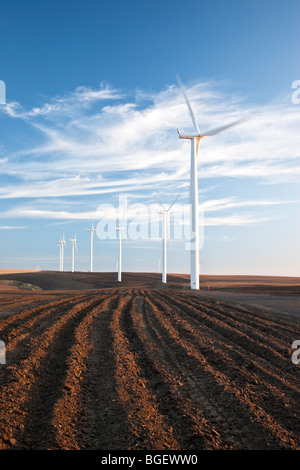 Wind Turbines operating in plowed field. - Stock Photo
