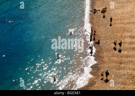 Aerial view of people on the beach and swimming in the sea at Durdle Door during British summertime - Stock Photo