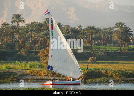 LUXOR, EGYPT. An evening felucca trip along the Nile, with the green and fertile west bank of the river behind. - Stock Photo