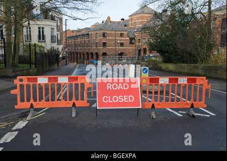 A road is blocked using barriers and a road closed sign. - Stock Photo