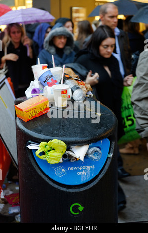 Overflowing public newspaper recycling bin with mixed waste. London. Britain. UK - Stock Photo