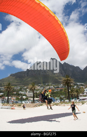 Paraglider landing at Camps Bay South Africa - Stock Photo