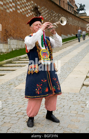 Busker playing in Polish National costume at the entrance slope to Wawel Hill (Wawel Cathedral / Wawel castle). - Stock Photo