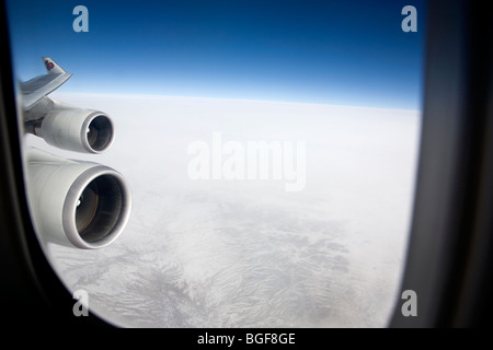 Thai Airplane flying over snowy terrain (Afghanistan) - Stock Photo