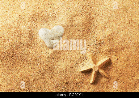 Heart Shaped Stone in Sand - Stock Photo