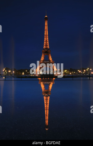 Eiffel tower reflected in water after dark in Paris, France. - Stock Photo