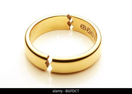 Broken Gold Wedding Ring Symbolizing Marriage Break Up - Stock Photo
