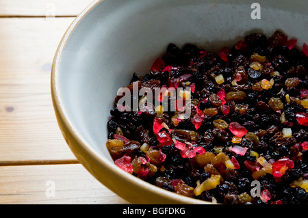 Dried fruit mixture in a bowl ready to go into a homemade Christmas cake, pudding or mince pies. - Stock Photo