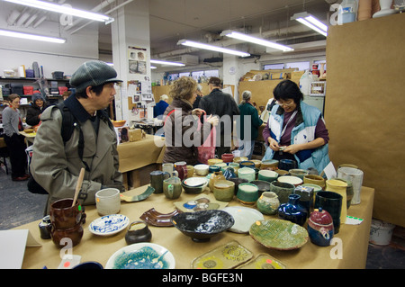 Members of a pottery studio in the New York neighborhood of Chelsea hold a holiday sale prior to Christmas - Stock Photo