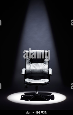 Empty Black Leather Chair under Spotlight Mastermind - Stock Photo