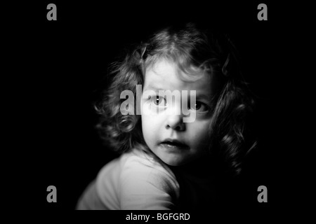 Black and white photo of a three year old girl in dramatic lighting. Black background. - Stock Photo