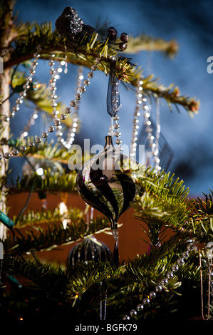 A swirling effect bauble placed precisely on a Christmas tree with other beautiful decorations in front of bay window. - Stock Photo