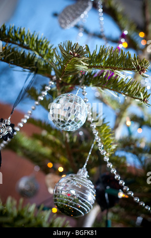 A colourful mini mirror-ball bauble dangling on a Christmas tree with other decorations in December in a bay window. - Stock Photo