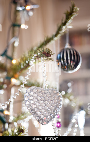 A colourful heart-shaped bauble decorations beautifully placed on a pine Christmas tree in a living room. - Stock Photo