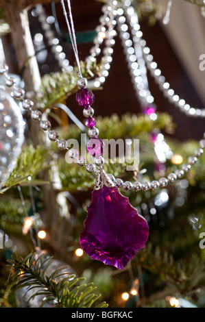 A glass pink bauble hangs on a Christmas tree with other collections of colourful decorations as Christmas. - Stock Photo