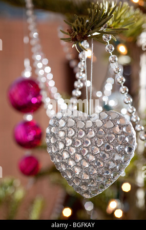A colourful heart-shaped bauble decorations beautifully placed on a pine Christmas tree with pink baubles behind. - Stock Photo
