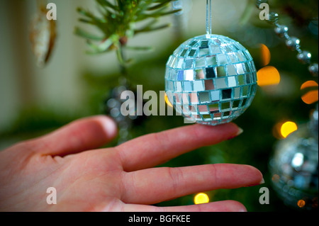 A mini mirror-ball is hand placed on a pine Christmas tree in a living room bay window in December. - Stock Photo