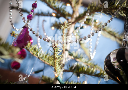 Colourful decorations beautifully placed on a pine Christmas tree in a living foom bay window in December. - Stock Photo