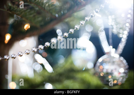 A length of silver decorative beading is draped on a pine Christmas tree, with a collection of other decorations - Stock Photo