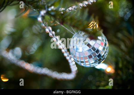 A mini disco-ball hangs on a Christmas tree with silver beads. - Stock Photo