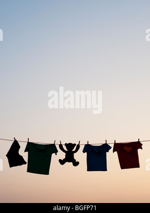 Childrens clothes and teddy bear on a washing line silhouette at dawn. India - Stock Photo