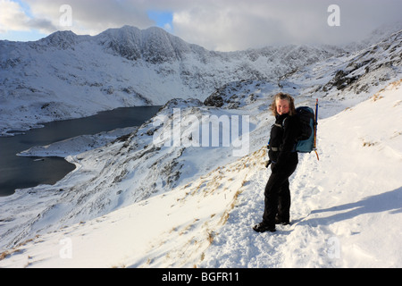 A female hill walker on Snowdon's Pyg Track under winter conditions. Views over to Llyn Llydaw and the peak of Y - Stock Photo
