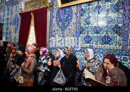 Women pray in front of the tomb of Eyuep Ensari, Eyuep , Istanbul, Turkey - Stock Photo