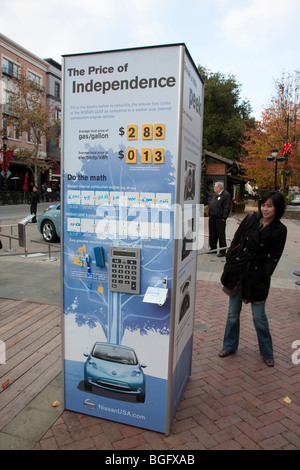 Woman reading poster about electric car Nissan Leaf that is scheduled to be released in Fall 2010. - Stock Photo