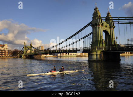 Rowers passing under Hammersmith suspension Bridge, River Thames, London, on a Winter's day