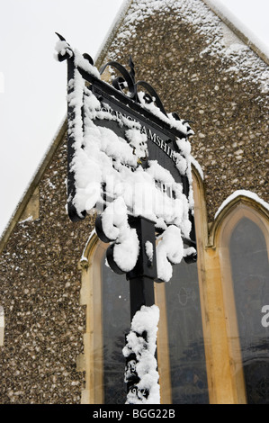 Buckinghamshire best kept village sign covered in Winter snow outside a church in Seer Green Bucks UK - Stock Photo