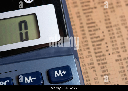 calculator with memory plus button focussed lying on a copy of the share prices in the financial times - Stock Photo