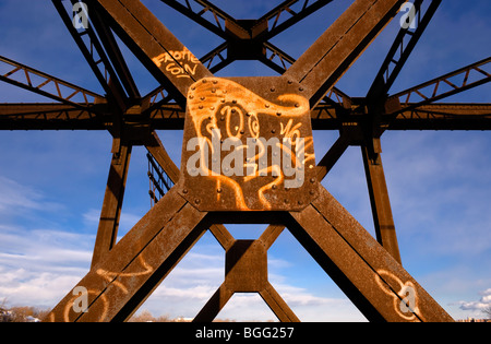 Graffiti on a rusty railway bridge on Rivière-des-Prairies, Laval, province of Québec, Canada - Stock Photo