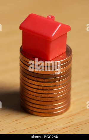 small model toy house on a stack of penny coins - Stock Photo