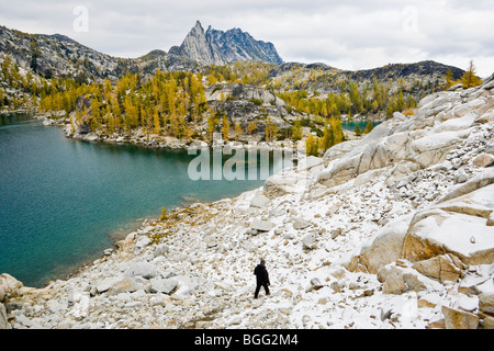 A view of a woman descending a talus field toward Inspiration Lake with Prusik Peak off in the distance, Enchantment - Stock Photo