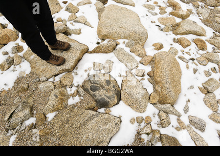 A persons legs and boots standing on a talus and snow slope, Enchantment Lakes Wilderness Area, Washington Cascades, - Stock Photo