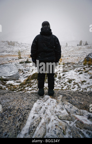 A person all dressed in black winter clothes looking out on a alpine landscape in a snow storm, Enchantment Lakes - Stock Photo