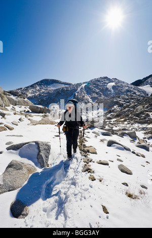 A woman wearing a backpack hiking in the snow through some high alpine landscape, Enchantment Lakes Wilderness Area - Stock Photo