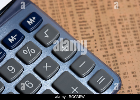 calculator with multiplication button focus lying on a copy of the share prices in the financial times Stock Photo
