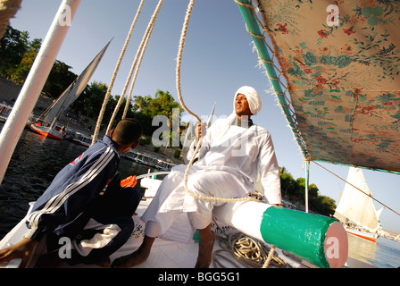 ASWAN, EGYPT. A boatman and his son on a Nile felucca, with Kitchener's Island behind. - Stock Photo