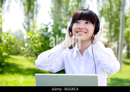 Woman in park with headset - Stock Photo