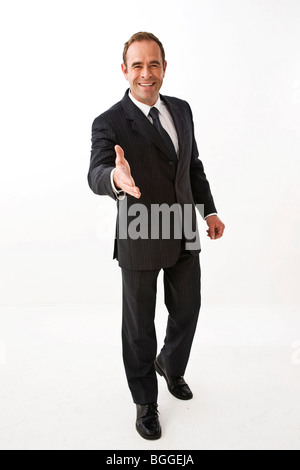 Businessman outstretching Hand for greeting, facing camera - Stock Photo
