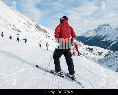 St Anton am Arlberg, Tyrol, Austria, Europe. Skier in red jacket on snow covered ski slopes in the Austrian Alps - Stock Photo