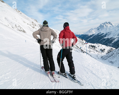 St Anton am Arlberg, Tyrol, Austria. Couple of skiers on snow covered ski slopes in the Austrian Alps. - Stock Photo
