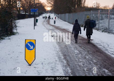 Parents and children walk uphill to school along a snowy Greendale, the cycle and pedestrian path in Dulwich, Southwark. - Stock Photo