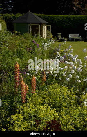 A garden flower border with summerhouse and seating - Stock Photo