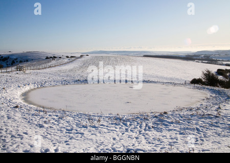 ditchling beacon and a frozen dew pond on the south downs - Stock Photo