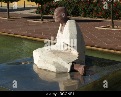 Silves town on the Algarve Portugal has these beautiful Tibetan statues on plinth  in a water setting. Sunny  Trees - Stock Photo