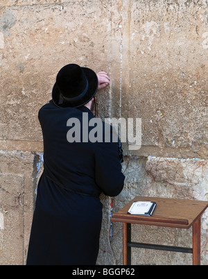 Religious Jew (known as Haredi) praying at  the Western or Wailing Wall (known as the Kotel) in Jerusalem Israel - Stock Photo