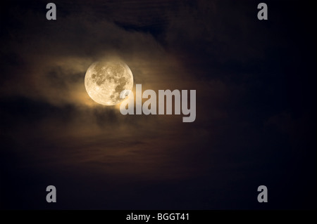 A dark night brings a bright, amber moon alive with puffy hazy clouds. - Stock Photo