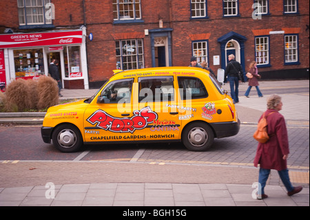 A yellow taxi cab drives through the city showing movement in Norwich,Norfolk,Uk - Stock Photo